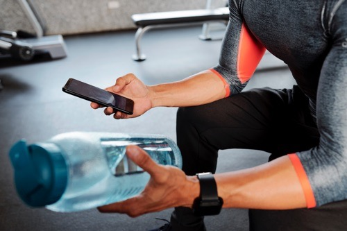 Close-up image of sportsman checking social media on smartphone and drinking water during break in gym